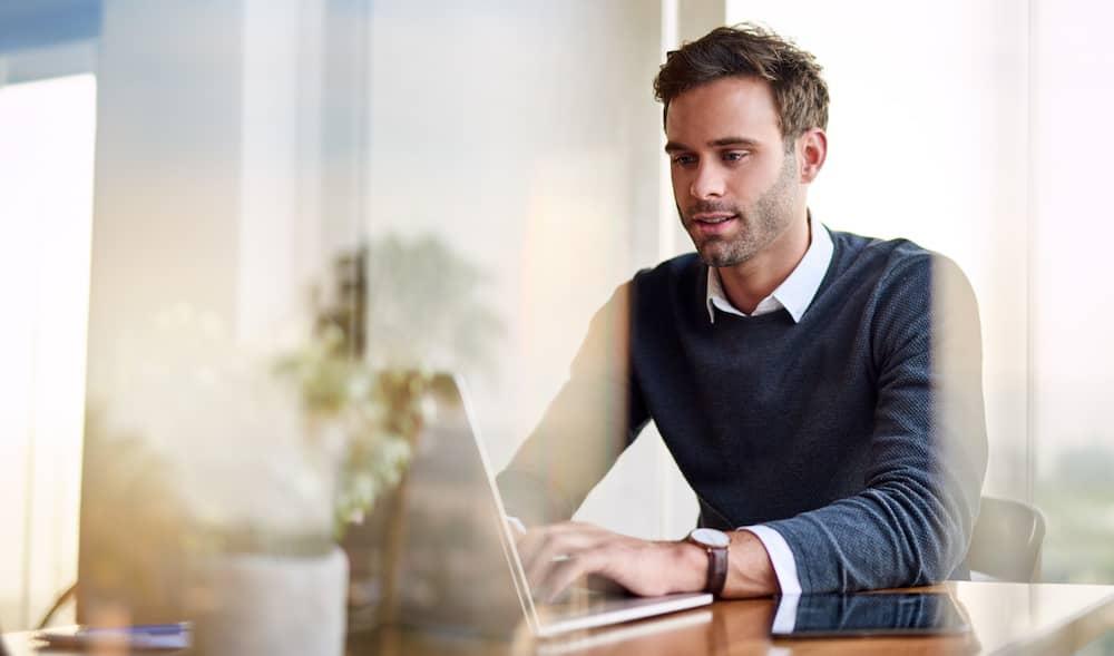 A businessman on a laptop facilitating a property deal..